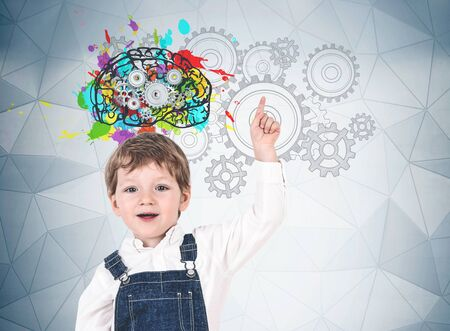 Adorable little boy in jeans overalls pointing up standing near gray wall with colorful brain sketch, cogs and gears. Concept of creative thinking, education and brainstorming Stockfoto