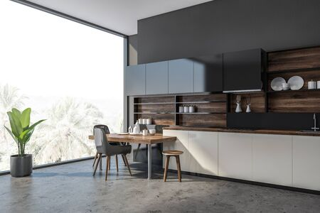 Corner of modern kitchen with concrete walls and floor, white countertops, black cupboards and stylish table with black chairs. 3d rendering