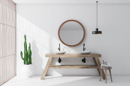 Interior of minimalistic bathroom with white walls and floor, light wooden blinds, double sink standing on wooden countertop and round mirror. 3d rendering