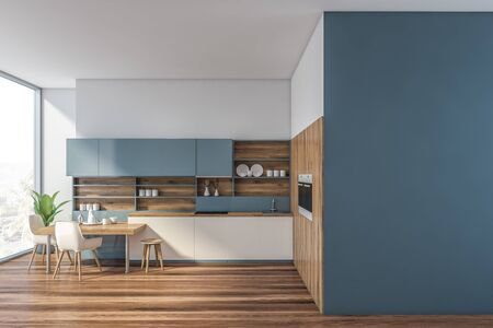 Interior of modern kitchen with white and blue walls, wooden floor, white countertops, blue cupboards, two built in ovens and stylish table with white chairs. Mock up wall to the right. 3d rendering