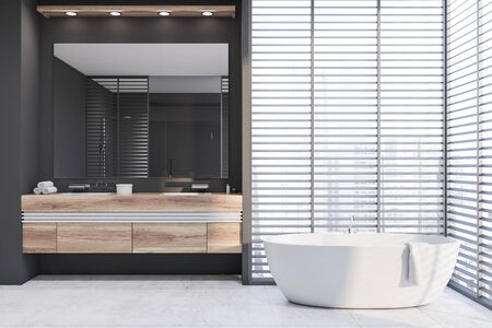 Interior of stylish bathroom with gray walls, tiled floor, comfortable white bathtub and double sink on wooden countertop with large mirror above it. 3d rendering