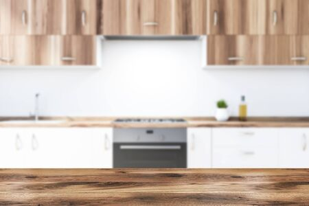 Close up of blurred white kitchen countertops with built in sink, cooker and oven and wooden cupboards above them in modern kitchen with white walls. Table for your product. 3d rendering