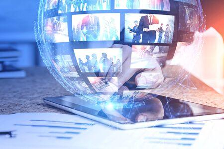 Mano dell'uomo che utilizza tablet con interfaccia di streaming video futuristica. Concetto di internet e social media. Doppia esposizione dell'immagine modificata. Elementi di questa immagine fornita dalla NASA