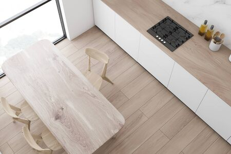 Top view of modern kitchen with white and marble walls, wooden floor, white countertops with built in cooker and wooden dining table with chairs. 3d rendering Stock fotó