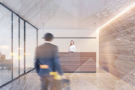 Businessman walking to office reception with smiling young secretary in modern office with white and wooden walls. Toned image double exposure blurred