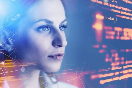 Beautiful young woman programmer looking at virtual screen with code and network interface. Concept of women in IT. Toned image double exposure blurred