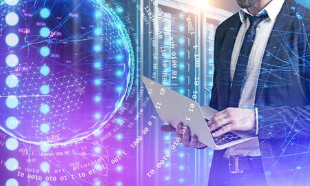 Unrecognizable man with laptop standing in modern data center with double exposure of planet hologram and binary numbers. Concept of coding. Toned image