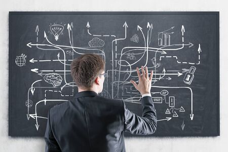 Rear view of young businessman in suit and glasses looking at blackboard with business plan sketch drawn on it. Concept of business strategy Stock Photo