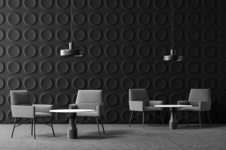 Interior of modern office lounge area with dark gray geometric pattern walls, concrete floor, comfortable gray armchairs near round coffee tables and stylish lamps. 3d rendering