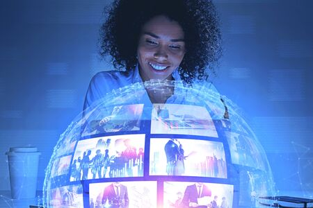 Sorridente giovane donna afroamericana che guarda l'interfaccia di streaming video futuristica. Concetto di alta tecnologia e social media. Doppia esposizione dell'immagine modificata. Elementi di questa immagine fornita dalla NASA Archivio Fotografico