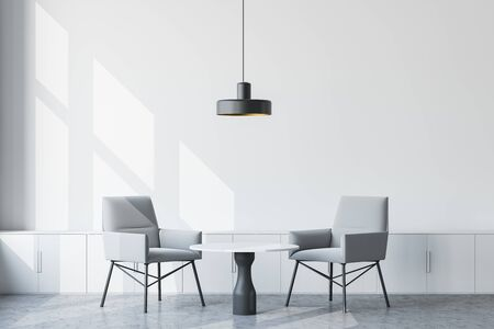 Interior of stylish industrial style office waiting room with white walls, concrete floor, gray armchairs near round coffee table and small cabinets with ceiling lamp above them. 3d rendering