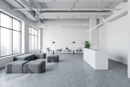 Interior of spacious industrial style office with white walls, concrete floor, reception desk with laptops and waiting room with armchairs, poufs and coffee tables. 3d rendering