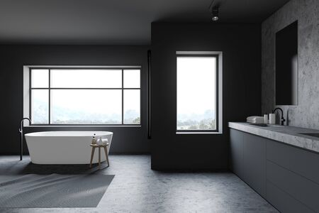 Interior of comfortable bathroom with gray and stone walls, stone floor, white bathtub and sink on grey countertop with vertical mirror. 3d rendering
