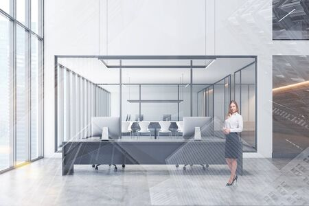 Smiling blonde businesswoman standing in modern open space office with white walls, concrete floor, long computer table and meeting room in background. Toned image double exposure
