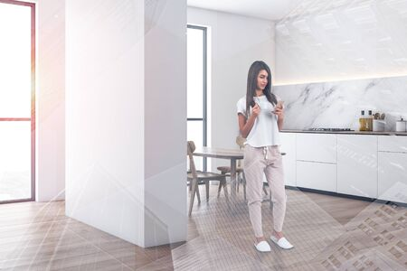 Young woman with phone and coffee standing in modern kitchen with white and marble walls, white countertops and wooden dining table with chairs. Toned image double exposure