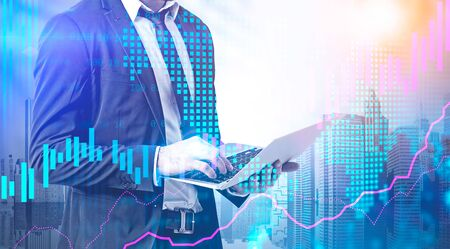 Businessman working with laptop in city with double exposure of digital graphs and world map. Concept of stock market and international business. Toned image