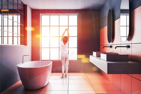 Rear view of woman in pajamas standing in modern bathroom with gray and orange tile walls, big window, double sink and comfortable white bathtub. Toned image double exposure