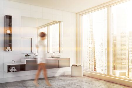 Woman walking in modern bathroom with white tile walls, panoramic window and double sink on gray countertop with three mirrors above it. Toned image blurred