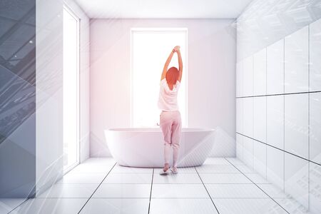 Rear view of woman in pajamas standing in minimalistic bathroom interior with white and tiled walls and comfortable bathtub. Toned image double exposure Stockfoto