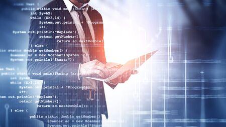 Ingeniero informático irreconocible con ordenador portátil con doble exposición de líneas de código. Concepto de programación y desarrollo de software. Imagen tonificada