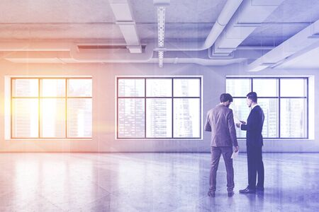Two businessmen discussing documents in empty industrial style office with white walls, concrete floor and large windows. Concept of starting new business. Toned image double exposure