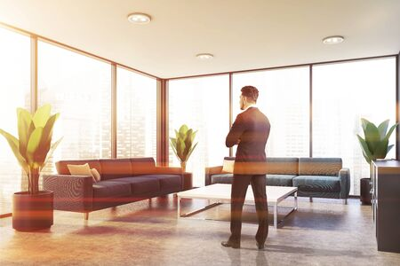Young businessman standing in panoramic office waiting room with blue sofas and square coffee table. Toned image Stockfoto