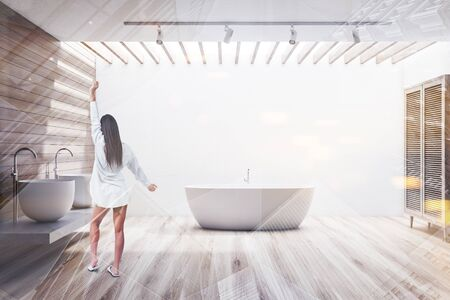 Rear view of woman in nightgown standing in modern bathroom with white and wooden walls, double sink on stone shelf and comfortable bathtub. Toned image double exposure