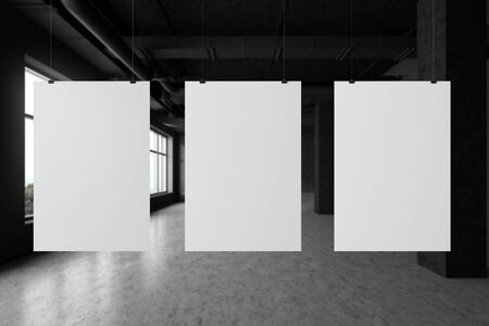 Three vertical mock up posters hanging on strings in modern blurred industrial style gallery with dark gray walls and concrete floor. Concept of advertising and art. 3d rendering Stockfoto