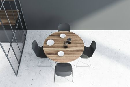 Top view of modern dining room with gray walls, concrete floor, round table with gray chairs and plates. 3d rendering