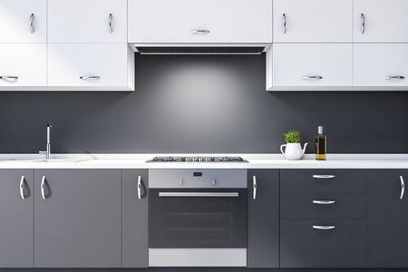Close up of gray kitchen countertops with built in sink, cooker and oven and white cupboards above them in modern kitchen with dark gray walls. 3d rendering