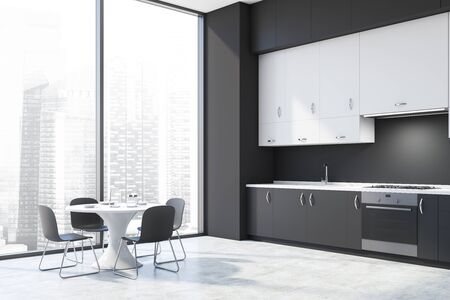 Corner of modern kitchen with dark gray walls, concrete floor, gray countertops, white cupboards and round dining table with chairs. 3d rendering