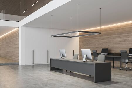 Interior of modern open space office with white and wooden walls, long gray computer table and row of smaller desks in background. 3d rendering