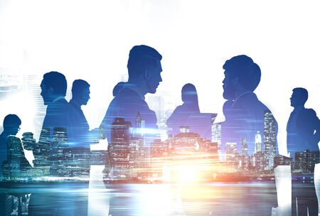 Silhouettes of diverse business people working together in night city. Concept of communication and teamwork. Toned image double exposure