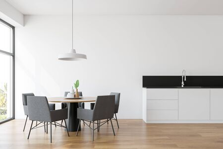 Interior of modern dining room and kitchen with white walls, wooden floor, round table with gray chairs and white countertop with built in sink. 3d rendering Stockfoto