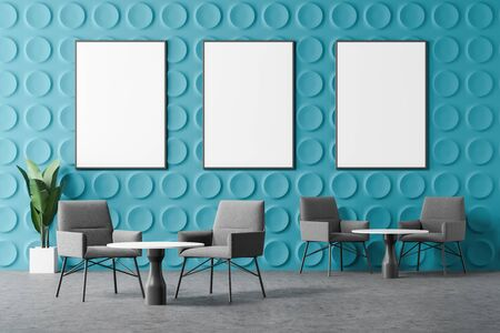 Interior of modern office lounge area with blue geometric pattern walls, concrete floor, comfortable gray armchairs near round coffee tables and vertical mock up posters. 3d rendering