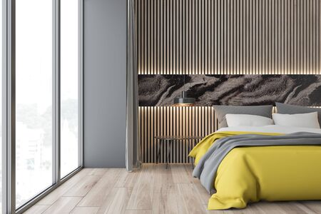 Interior of stylish bedroom with gray and wooden walls, wooden floor, king size bed with yellow blanket and bedside table near panoramic window. 3d rendering Zdjęcie Seryjne