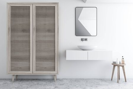 Interior of stylish bathroom with white walls, concrete floor, sink standing on white counter with small mirror above it and wooden wardrobe. 3d rendering