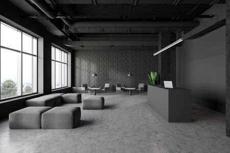 Interior of spacious industrial style office with dark gray walls, concrete floor, reception desk with laptops and waiting room with armchairs, poufs and coffee tables. 3d rendering