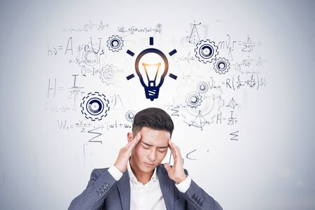 Stressed Asian man thinking hard standing near white wall with formulas written on it. Concept of scientific discovery