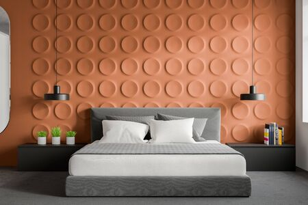 Interior of stylish bedroom with orange geometric pattern walls, concrete floor with carpet, king size bed and two gray bedside tables. 3d rendering