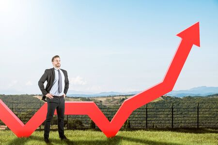 Confident young businessman standing near growing graph in meadow and beautiful mountain view. Concept of business success