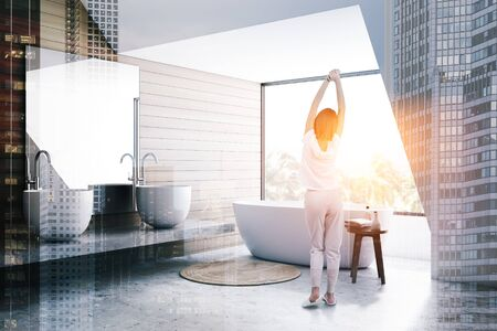 Woman in pajamas standing in stylish bathroom interior with white and wooden walls, double sink on stone shelf and comfortable bathtub. Toned image double exposure Zdjęcie Seryjne