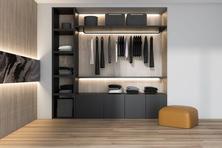 Black wardrobe with clothes standing in stylish bedroom interior with white and wooden walls, wooden floor and leather armchair. 3d rendering