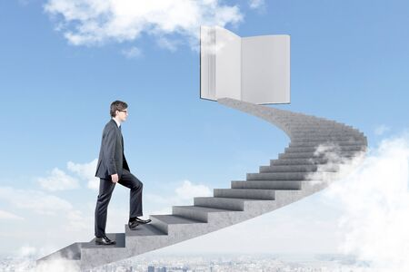 Young man in glasses climbing staircase in sky leading to large book. Cityscape below him. Concept of knowledge and education.