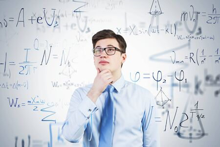 Portrait of pensive young man in glasses standing near white wall with formulas written on it. Concept of education and science. Toned image double exposure Stockfoto