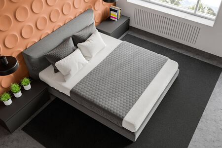 Top view of stylish bedroom with orange geometric pattern and white walls, concrete floor with carpet, king size bed and two gray bedside tables. 3d rendering Zdjęcie Seryjne