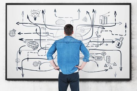 Rear view of young man in casual clothes looking at whiteboard with business plan sketch drawn on it. Concept of business strategy