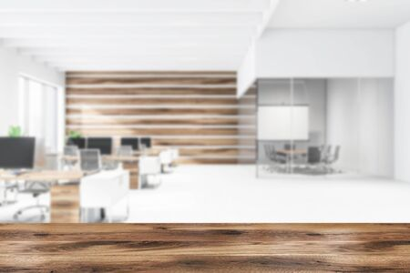 Blurred interior of open space office with white and wooden walls, conference room with projection screen and rows of wooden computer tables with black chairs. Table for your product. 3d rendering