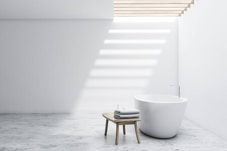 Interior of spacious bathroom with white walls, concrete floor, comfortable white bathtub and chair with towels and shampoos. 3d rendering Zdjęcie Seryjne