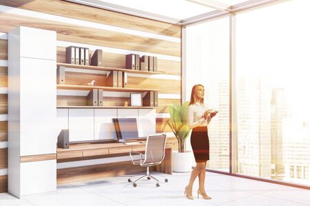 Pensive blonde businesswoman standing in modern office with white and wooden walls, panoramic window, computer table and shelves with folders. Toned image